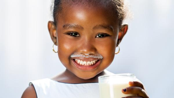 image of smiling child holding a glass of milk