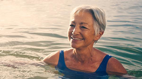 image of an older woman in the sea swimming