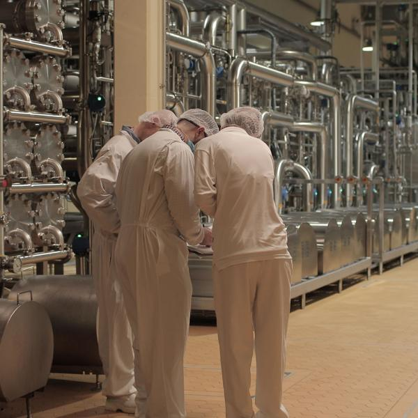 Three employees in white overalls working in a Glanbia Ireland factory discussing quality