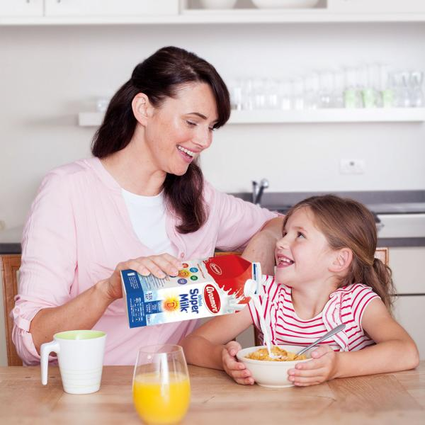 Mother pouring Avonmore Supermilk into her daughter's bowl of cereal